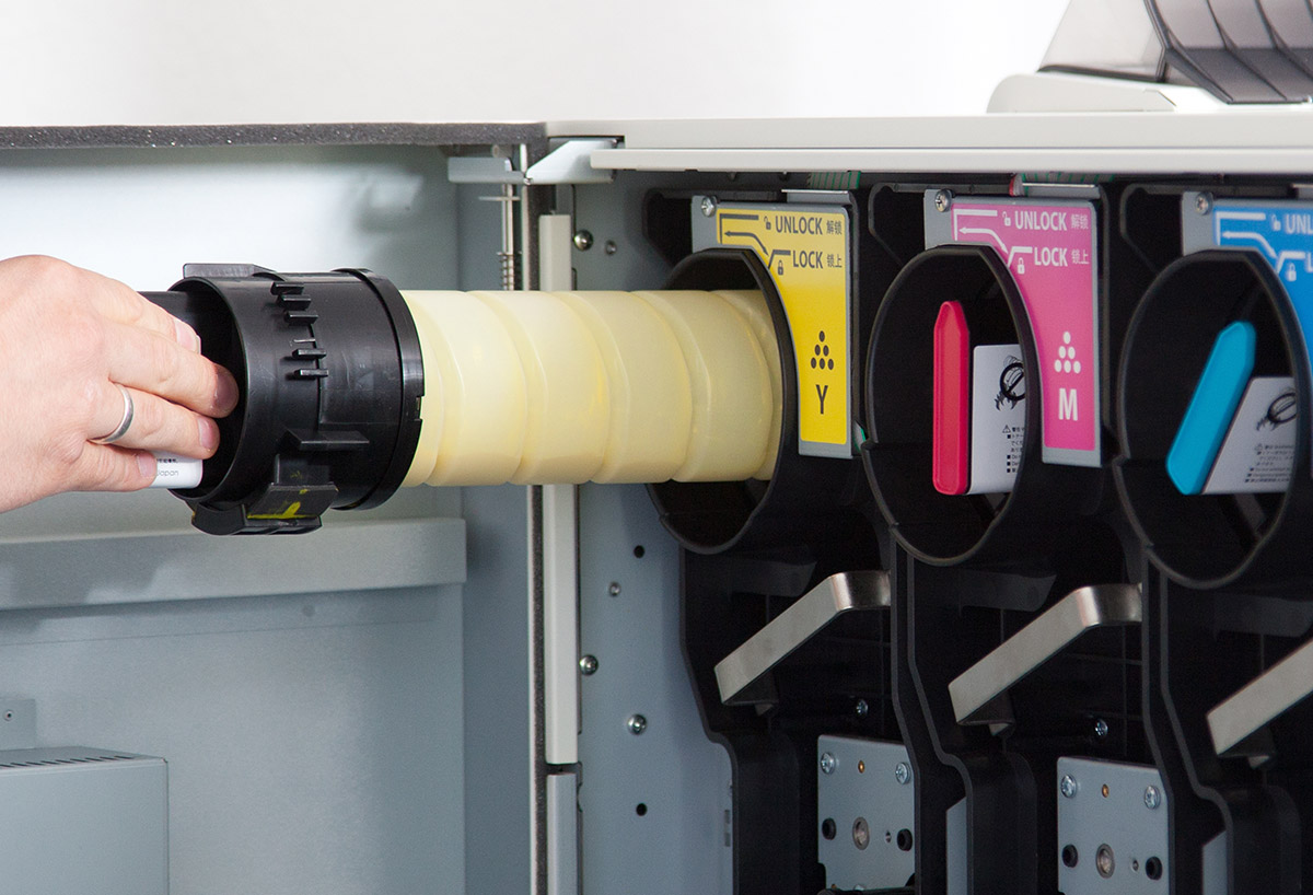 Eine Hand tauscht den gelben Toner eines Druckers aus