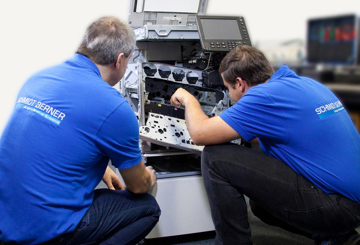 Zwei Servicetechniker arbeiten an einem Drucker