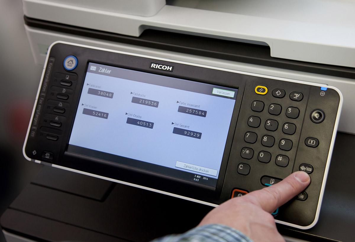Eine Hand bedient das Steuerungsfeld eines Druckers. Der Display zeigt den Zählerstand.